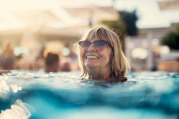 Portrait of a happy senior woman enjoying swimming pool Happy senior woman enjoying summer vacations. The woman is swimming in the pool. Nikon D850 real life stock pictures, royalty-free photos & images