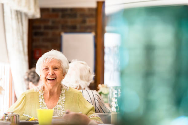 Portrait of a happy senior woman in her mid 80ties having lunch in a dinning room stock photo