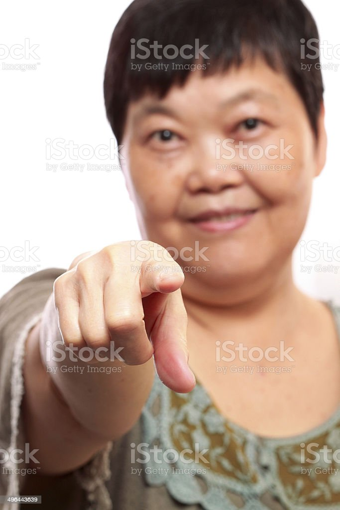 Portrait of a happy senior woman pointing forwards on white. royalty-free stock photo