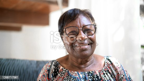 istock Portrait of a happy senior woman standing at home 1268717561