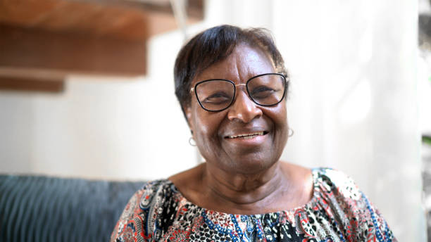 Portrait of a happy senior woman standing at home stock photo