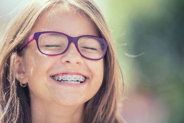 porträt eines glücklich lächelnden mädchens mit zahnspangen und gläser. - kieferorthopäde stock-fotos und bilder