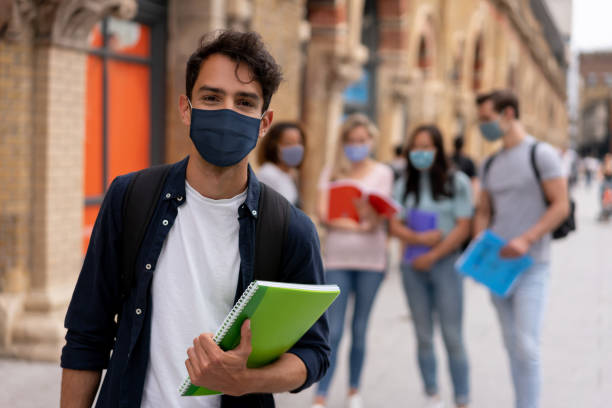 Portrait of a happy student wearing a facemask on the street stock photo