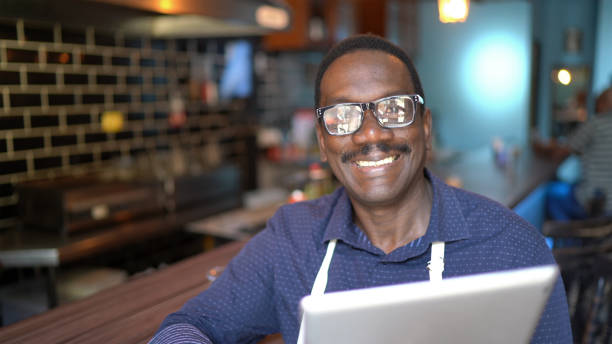 Portrait of a happy waiter using digital tablet in a pub Portrait of a happy waiter using digital tablet in a pub old man working in a pub stock pictures, royalty-free photos & images