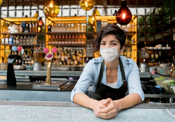 Portrait of a happy waitress working at a restaurant wearing a facemask stock photo