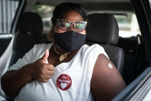 Portrait of a happy woman in a car with a 'get vaccinated' sticker - wearing face mask stock photo