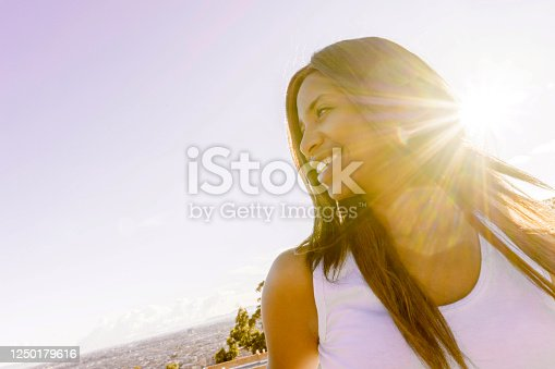Portrait of a happy black woman outdoors with the sunshine at the background and smiling - lifestyle concepts
