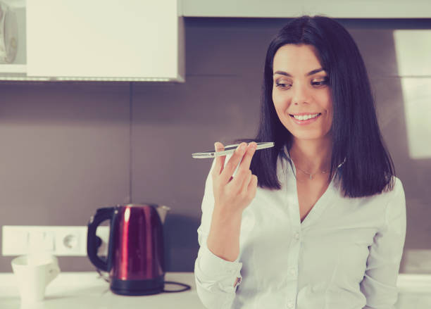Portrait of a happy woman using the voice recognition of the phone standing in kitchen of a house stock photo