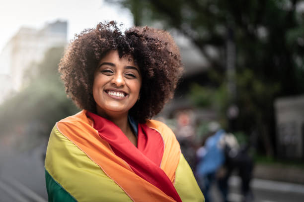 Portrait of a happy woman wearing the rainbow flag stock photo