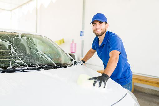 I like my job at the car wash. Attractive young man smiling and making eye contact while washing a car at his job at the auto detail