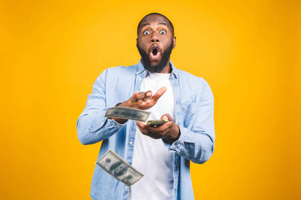 portrait of a happy young afro american man throwing out money banknotes isolated over yellow background. - throw money away stock pictures, royalty-free photos & images