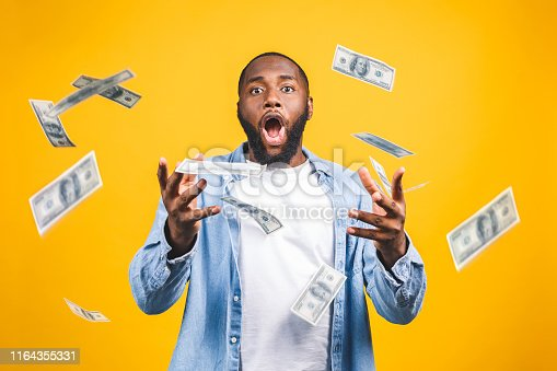 istock Portrait of a happy young afro american man throwing out money banknotes isolated over yellow background. 1164355331