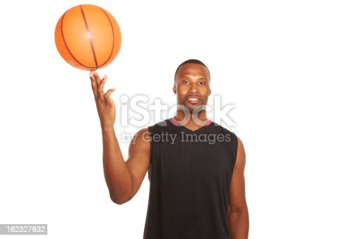 portrait of a happy young basketball player spinning ball on finger isolated on white.