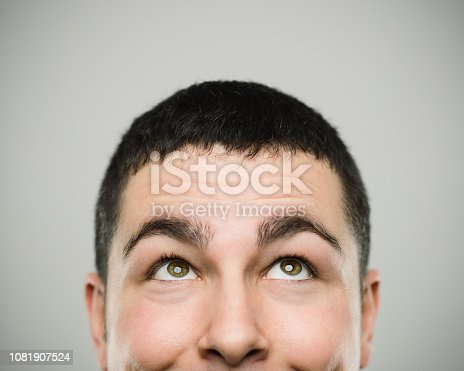 Close-up portrait of real young man smiling and looking up. Caucasian male has brown hair and happy expression. He is against gray background. Horizontal studio photography from a DSLR camera. Sharp focus on eyes.