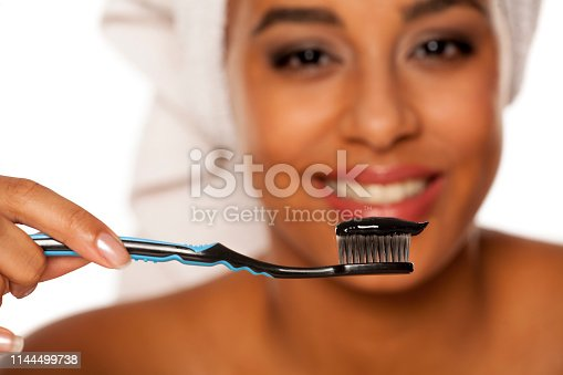 portrait of a happy young dark-skinned woman posing with toothbrush and black tooth paste on a white background