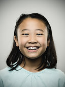 Studio portrait of a happy japanese young girl with relaxed expression smiling at camera. The girl has 10 years and has long hair and casual clothes. Vertical color image from a medium format digital camera. Sharp focus on eyes.
