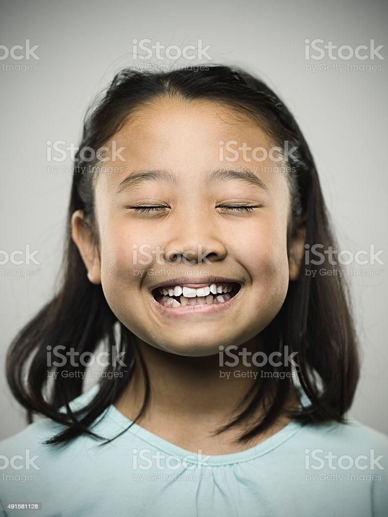 Portrait of a happy young japanese girl smiling at camera. stock photo