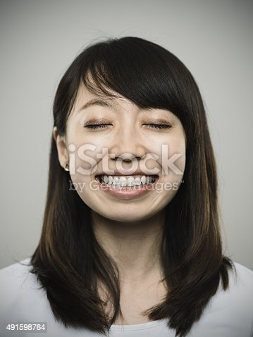 istock Portrait of a happy young japanese woman looking at camera 491598764