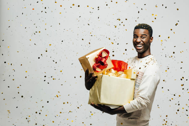 portrait of a happy young man laughing and holding gold and red gifts as golden confetti are falling - carlos david stock pictures, royalty-free photos & images