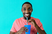Portrait of a happy young man smiling and drinking with a paper straw from a plastic cup, against blue studio background