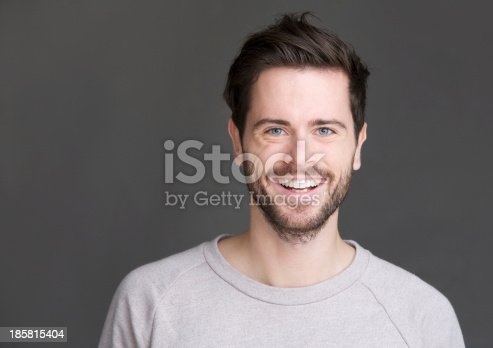 istock Portrait of a happy young man smiling on gray background 185815404