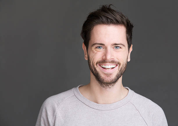 portrait of a happy young man smiling on gray background - one young man only stock photos and pictures
