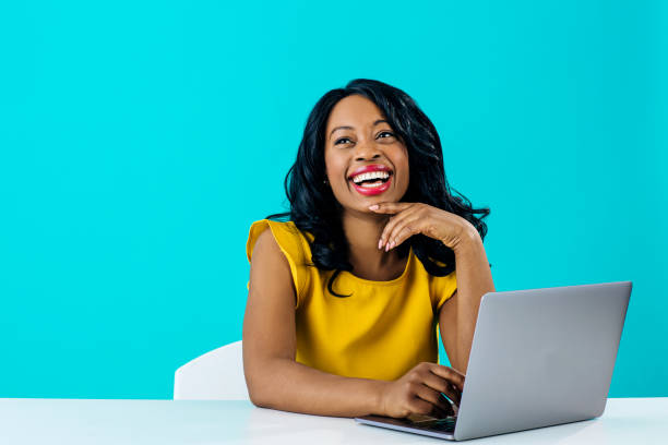 portrait of a happy young smiling woman sitting behind desk and computer laptop, looking up - carlos david stock pictures, royalty-free photos & images