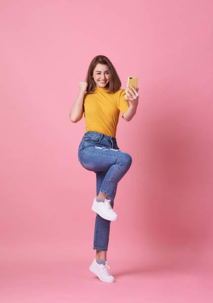 Porträt einer glücklichen jungen Frau, die mit dem Handy isoliert über rosa Hintergrund feiert. – Foto