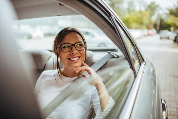 Retrato de una joven feliz en el asiento trasero del coche mirando por la ventana. - foto de stock