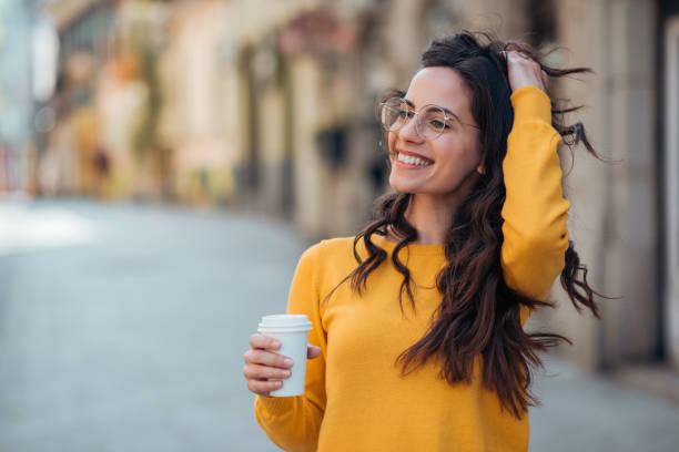 Porträt einer glücklichen jungen Frau in der Stadt hält Take-out-Drink. – Foto