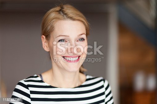istock Portrait of a happy young woman looking away. She smiling. 1132337381