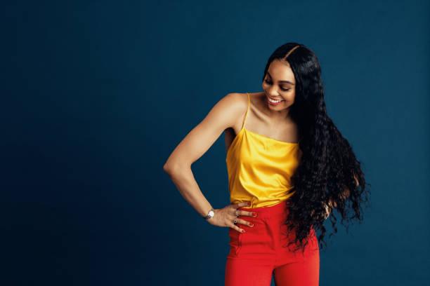 porträt einer glücklichen jungen frau mit sehr langen schönen schwarzen lockigen haaren lächelnd mit einem arm auf der taille - haarverlängerung stock-fotos und bilder