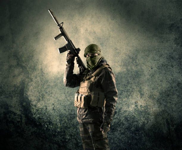 Portrait of a heavily armed masked soldier with grungy background Portrait of a heavily armed masked soldier with grungy background concept terrorism stock pictures, royalty-free photos & images