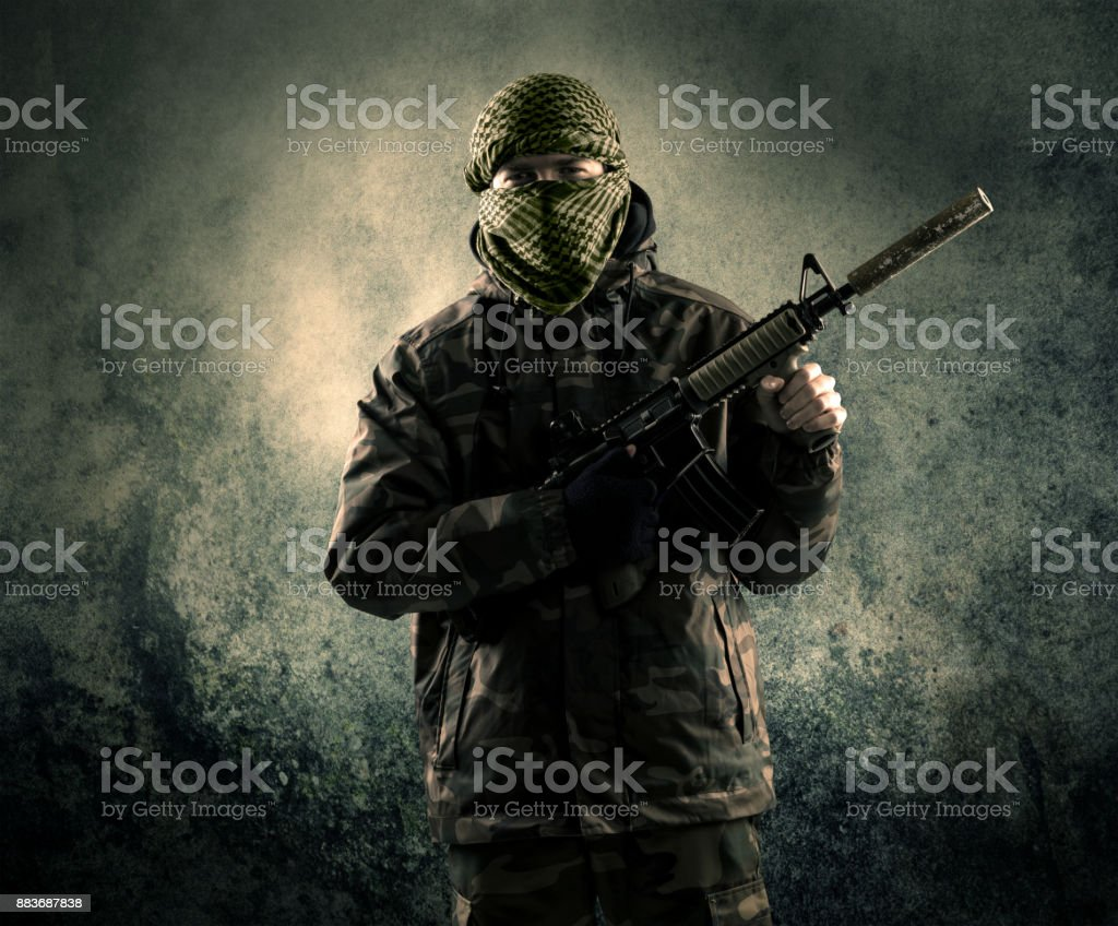 Portrait of a heavily armed masked soldier with grungy background stock photo