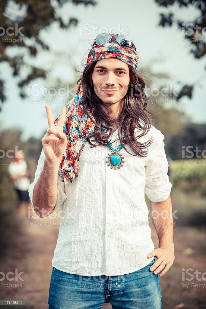 Portrait of a hippie with long hair showing a peace sign stock photo
