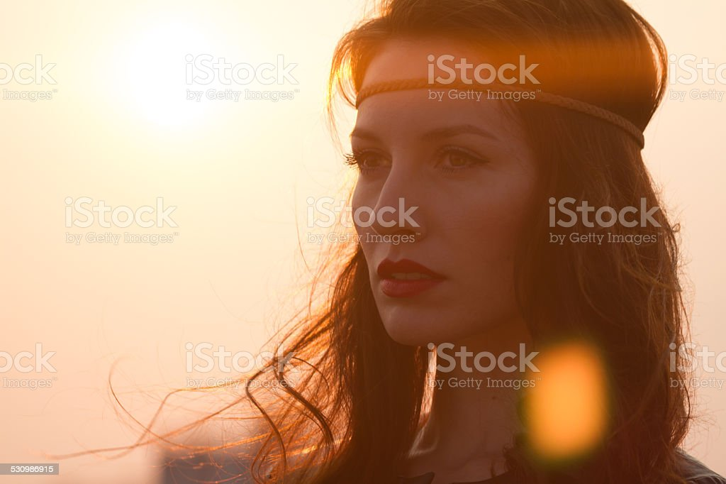 Portrait of a hippie woman with headband looking far away stock photo