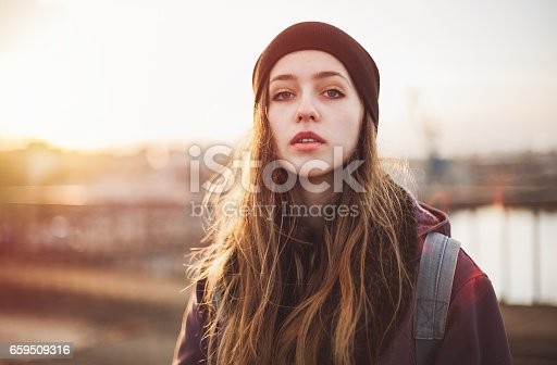 Portrait of a serious hipster girl at sunset