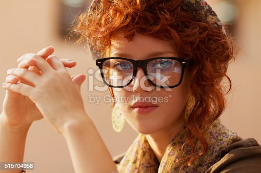 Portrait of young hipster girl in reading glasses and fance hat looking in the camera