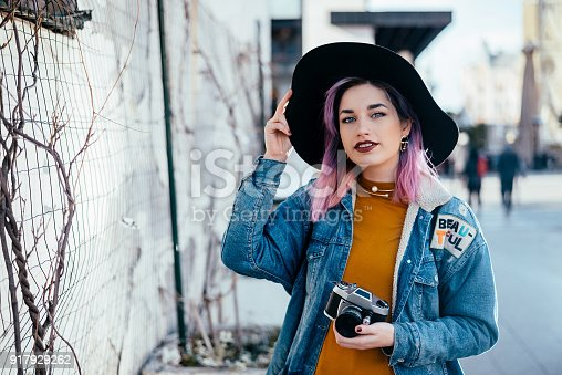 Portrait of a hipster girl with a hat at city street.