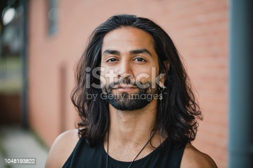 Close up portrait of a mid-adult mixed race man.