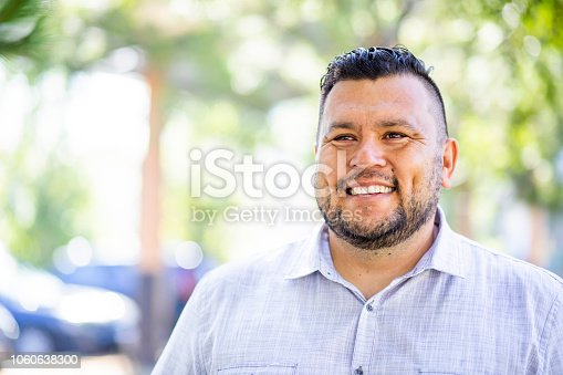 A young hispanic man smiles outdoors
