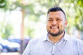 A young hispanic man smiles outdoors