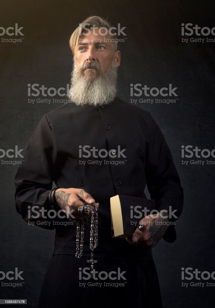 Portrait of a holy priest in front of a dark background stock photo