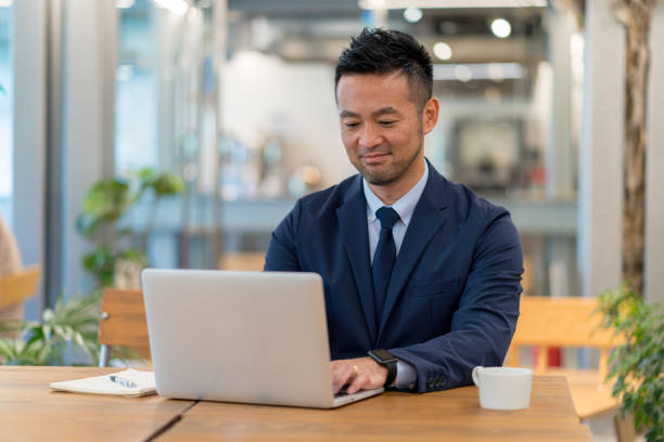 彼のラップトップを使用して、日本のビジネスマンの肖像 - パソコン 日本人 ストックフォトと画像