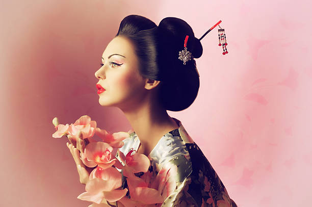 portrait of a japanese geisha woman with flower - geisha girl stock photos and pictures