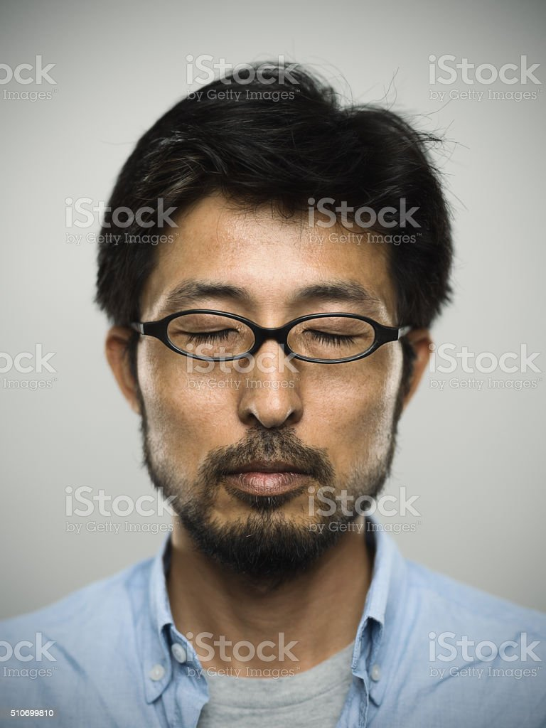d426824c8d4d Portrait of a japanese man with closed eyes wearing glasses - Stock image .