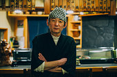 Portrait of a real Japanese Sushi Chef in Tokyo, Japan. The man is folding his arms and looking at the camera while standing in his family owned sushi restaurant.