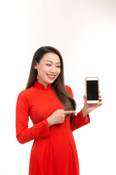 portrait of a joyful asian woman showing blank screen mobile phone isolated over white background - ao dai stock photos and pictures