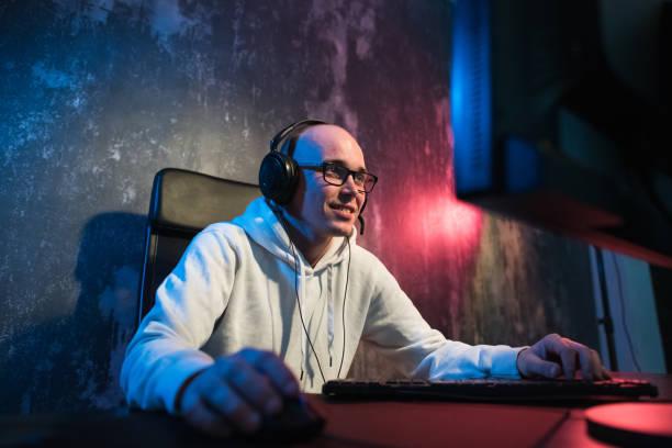 うれしそうな若いコンピューター上自宅でビデオ ゲームを遊ぶゲーマーの肖像画。ヘッドフォンでゲーマー幸せで示すジェスチャー親指は、彼はゲームを獲得しました。コンピューター ゲ� - ゲーム ヘッドフォン ストックフォトと画像