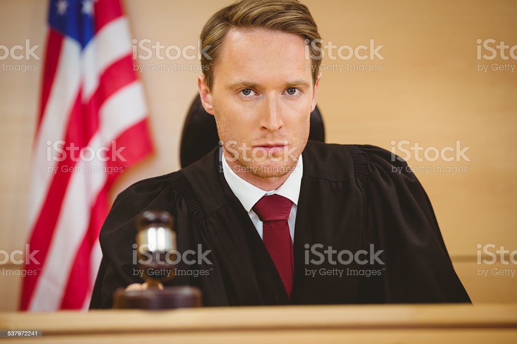 Portrait of a judge about to bang gavel stock photo